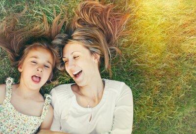 Fototapeta Cute little girl i jej matka zabawy na trawie w słoneczny