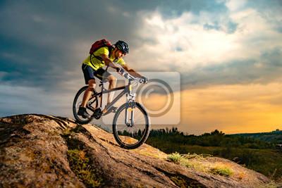 Fototapeta Cyclist Riding the Mountain Bike on Rocky Trail at Sunset. Extreme Sport and Enduro Biking Concept.