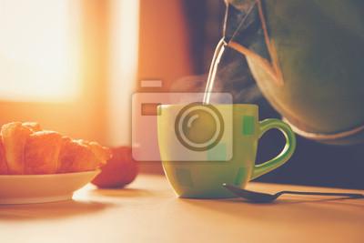 Czajnik wylewanie wrzącej wody do kubka podczas śniadania w poranek