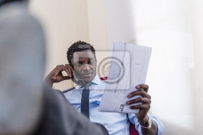 Czarny biznesmen siedzi rozmawia przez telefon