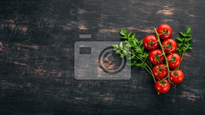Fototapeta Czereśniowi pomidory na gałązce. Widok z góry. Na czarnym tle drewnianych. Skopiuj miejsce.