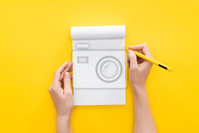 Fototapeta częściowy widok osoba trzyma długopis na pustym notatniku na żółtym tle