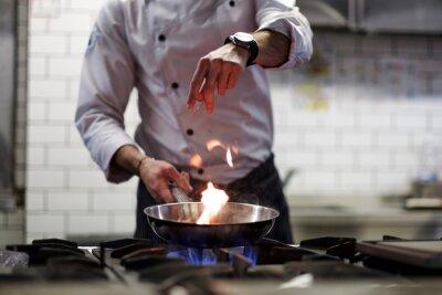 Fototapeta Człowiek gotuje gotować głębokie frytkownicy w kuchni ognia.