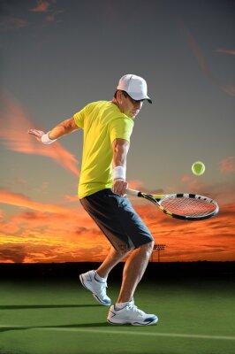 Fototapeta Człowiek gra w tenisa na zachód słońca