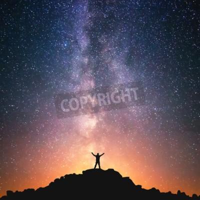 Fototapeta Człowiek i Wszechświat. Osoba stoi na szczycie wzgórza obok Drogi Mlecznej z rękami podniesione do powietrza.
