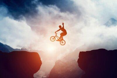 Fototapeta Człowiek skoków na rower BMX nad przepaścią w górach na zachodzie.