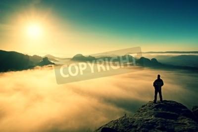 Fototapeta Człowiek stoi na szczycie skały piaskowca w parku narodowym Saksonii Szwajcarii i oglądać do Sun. Piękny moment cud natury