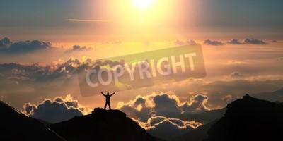 Fototapeta Człowiek stojący na szczycie góry ponad chmurami.