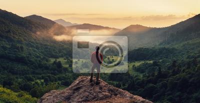 Fototapeta Człowiek stojący na szczycie urwiska o zachodzie słońca