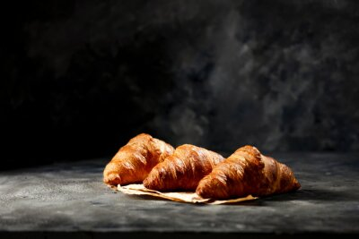 Dark mood background and fresh croissants on board.Free space for your decoration and breakfast time.