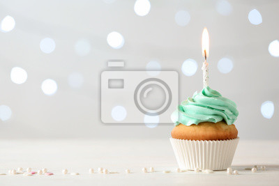 Fototapeta Delicious birthday cupcake with burning candle and space for text on blurred lights background