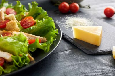 Fototapeta Delicious Caesar salad with cherry tomatoes and croutons and piece and grated parmesan cheese on black serving board.