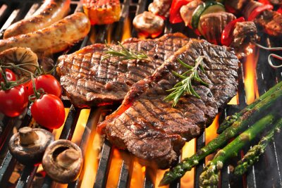 Fototapeta Delicious grilled meat with vegetables sizzling over the coals on barbecue