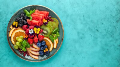 Fototapeta Delicious healthy salad of fresh fruits, berries and edible flowers on plate. Clean eating. Top view.