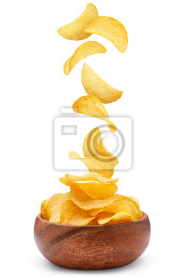 Fototapeta Delicious potato chips falling into a wooden bowl, isolated on white background