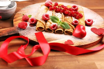Delicious Tasty Homemade crepes or pancakes with raspberries and mint on rustic background