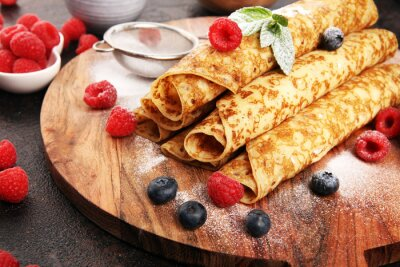 Fototapeta Delicious Tasty Homemade crepes or pancakes with raspberries and mint on rustic background