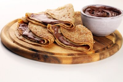 Delicious Tasty Homemade crepes with chocolate or pancakes on rustic wood