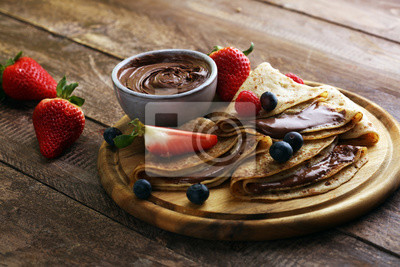 Delicious Tasty Homemade crepes with chocolate or pancakes with raspberries and blueberries on rustic wood
