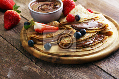 Fototapeta Delicious Tasty Homemade crepes with chocolate or pancakes with raspberries and blueberries on rustic wood