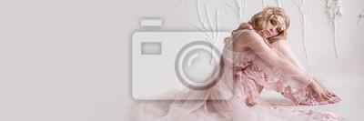 Fototapeta Delikatny portret młodej dziewczyny model. Wizerunek panny młodej, lekka koronkowa sukienka w kolorze różowym, piękna fryzura i naturalny makijaż. Lekkie studio fotograficzne, naturalne światło z okna