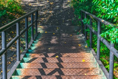 Fototapeta Descending an old and rusty iron staircase to an autumn park with still green leaves on the trees