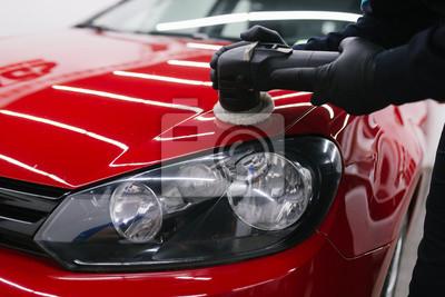 Fototapeta Detal samochodu - Człowiek z polerką orbitalną w warsztacie polerującym w warsztacie samochodowym. Selektywne ustawianie ostrości.