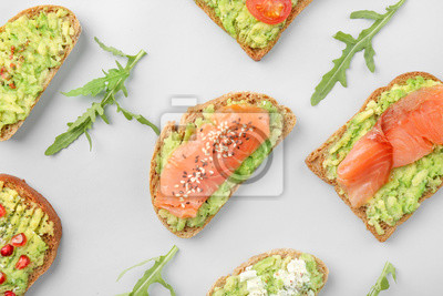 Fototapeta Different tasty avocado toasts on grey background