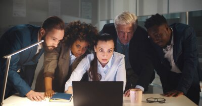 Fototapeta Diverse group of business people in office at night looking at laptop screen