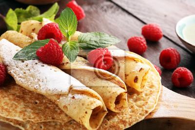 Domowe naleśniki podane ze świeżymi raspberrries i cukrem pudrem na rustykalnym stole.