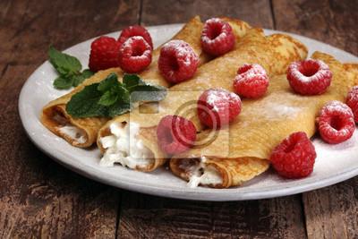 Domowe naleśniki podawane z świeżego raspberrries i sproszkowanego cukru na rustykalnym drewnianym stole