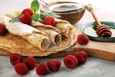 Domowe naleśniki podawane ze świeżymi malinami i cukrem pudrem na rustykalnym stole.