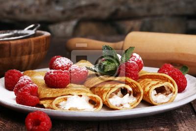 Domowe naleśniki podawane ze świeżymi raspberrami i sproszkowanym cukrem na rustykalnym drewnianym stole