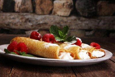 Domowe naleśniki podawane ze świeżymi raspberrries i pudrem cukrowym na rustykalnym drewnianym stole