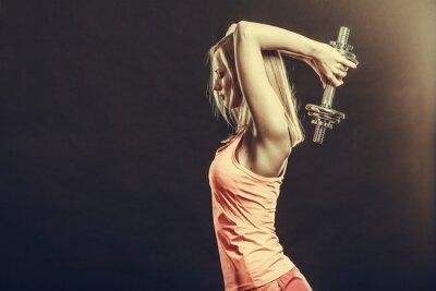Fototapeta Dopasuj kobieta ćwiczenia z hantlami.