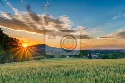 Fototapeta Doskonałym Wiosna dzień kończy się jak słońce i spraye ciepłe złote światło nad pięknym gospodarstwie z pól kiełkowanie, kamiennicy i grzbietów górskich w tle.