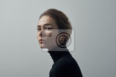Fototapeta Dramatyczny portret młodej pięknej dziewczyny z piegami w czarnym golfie na białym tle w studio