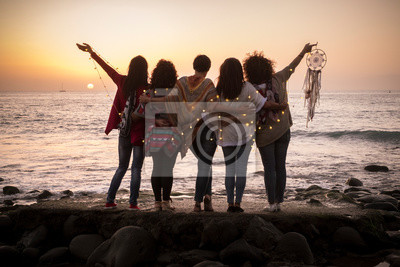 Fototapeta Dreaming image with group of females friends hug each other all together looking the sunset for friendship and love concept - Forever friends and dream lifestyle concept - people enjoying and feeling