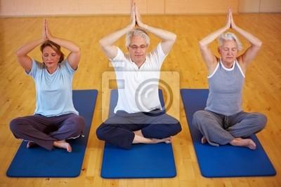 Drei Menschen machen Yoga