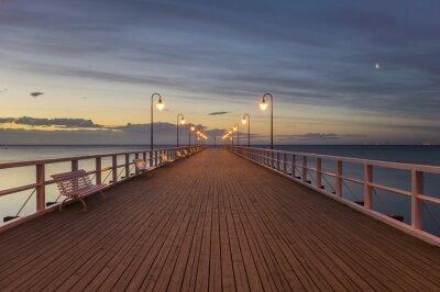 Fototapeta drewniane molo nad morzem oświetlone stylowymi lampami w nocy