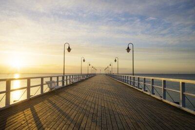 Fototapeta Drewniane molo w morzu o wschodzie słońca