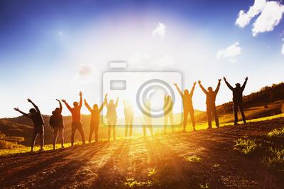 Fototapeta Duża grupa przyjaciół, podnosząc ręce na zachodzie słońca razem