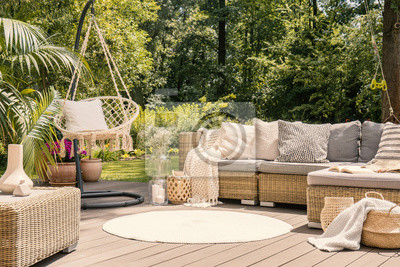 Fototapeta Duży taras z wygodną sofą wypoczynkową z poduszkami, stołem i huśtawką w zielonym ogrodzie podczas słonecznych wakacji.