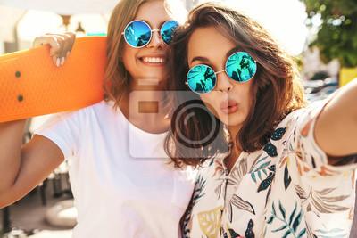 Fototapeta Dwa młodej żeńskiej eleganckiej hipis brunetki i brunetki kobiet modela w lato modnisiu odziewają brać selfie fotografie dla ogólnospołecznych środków na smartphone na ulicznym tle. Z kolorowymi desko