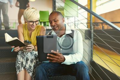 Fototapeta Dwa twórczych millenial właścicieli małych firm pracujących na strategii mediów społecznych przy użyciu cyfrowego tabletu siedząc w klatce schodowej