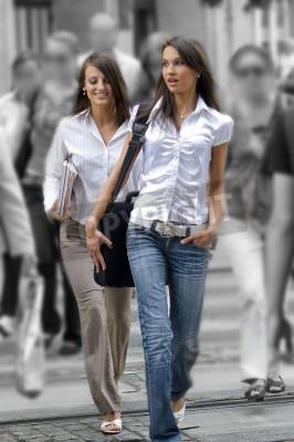 dwie młode kobiety między tłumem przechodzącym przez ulicę w centrum miasta
