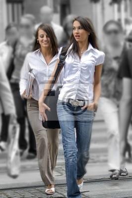 dwie młode kobiety między tłumu skrzyżowania dróg