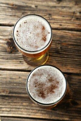 Fototapeta Dwie szklanki piwa na brązowym tle drewnianych