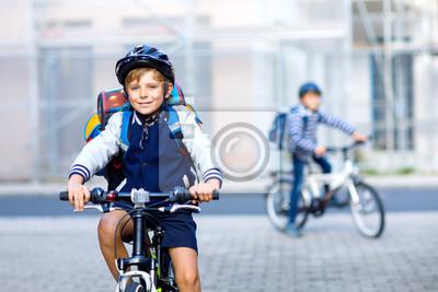 Fototapeta Dwóch chłopców ze szkoły w jeździe na rowerze z rowerami w mieście z plecakami. Szczęśliwe dzieci w kolorowych ubraniach na rowerach w drodze do szkoły. Bezpieczny sposób dla dzieci na zewnątrz do szk