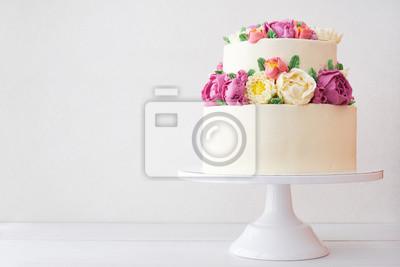 Fototapeta Dwupoziomowy biały tort weselny ozdobiony kremowymi kwiatami na białym tle drewnianych.